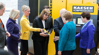 Mrs Vlantoussi-Kaeser presents the German Chancellor, Angela Merkel, with a model of a compressor.